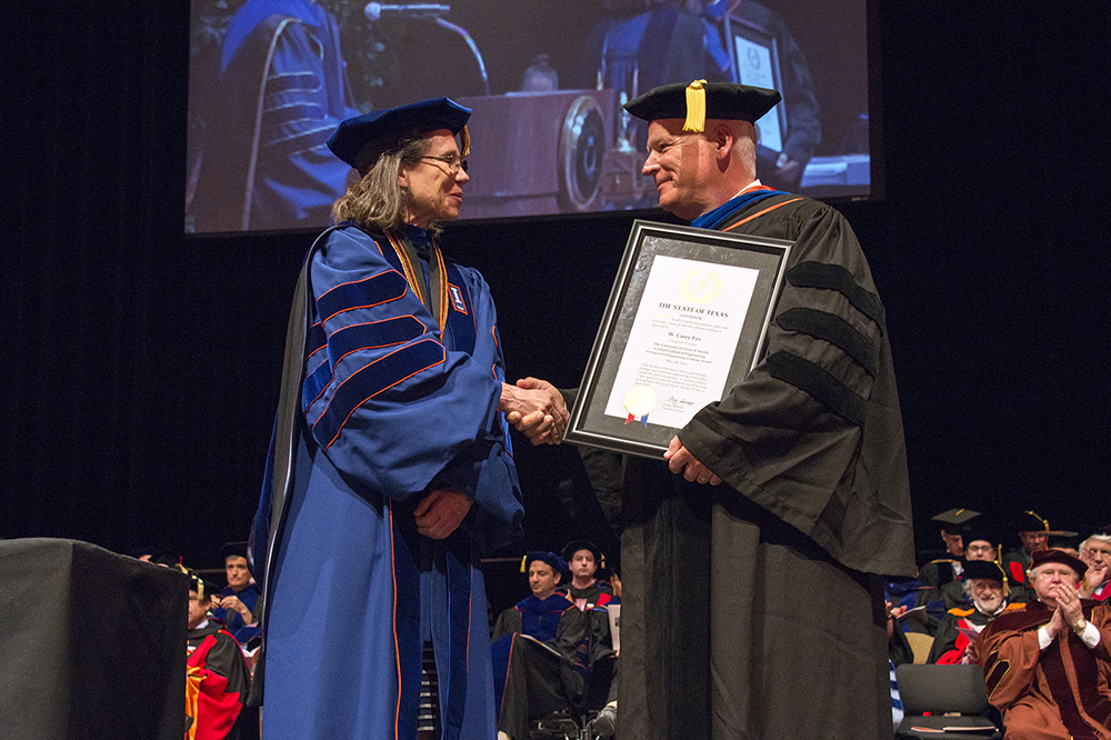 Dean Sharon Wood shakes hands with a distinguished engineering graduate award recipient at the 2018 commencement ceremony