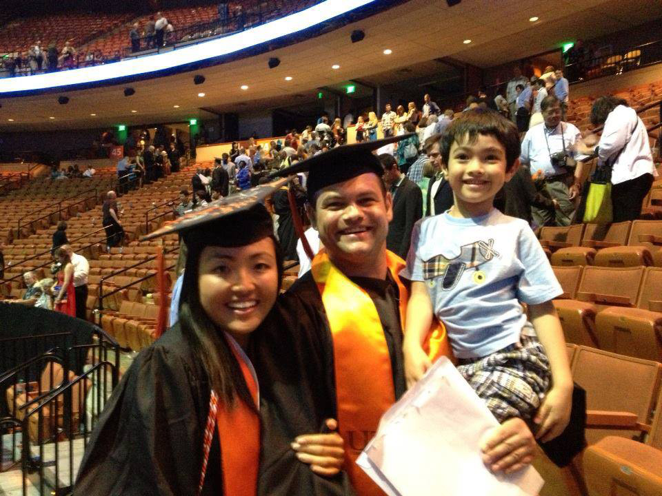 Ru and Peter pose in their cap and gowns while holding their toddler-aged son at the Texas Engineering graduation ceremony in 2013.