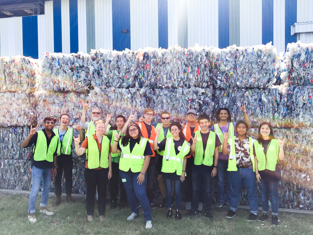 Students pose in front of blocks of recycled materials.