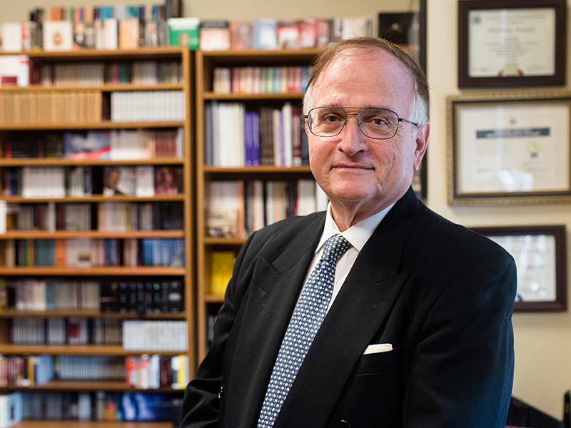 Portrait of Nicholas Peppas in his office in front of a book shelf filled with CDs and records.