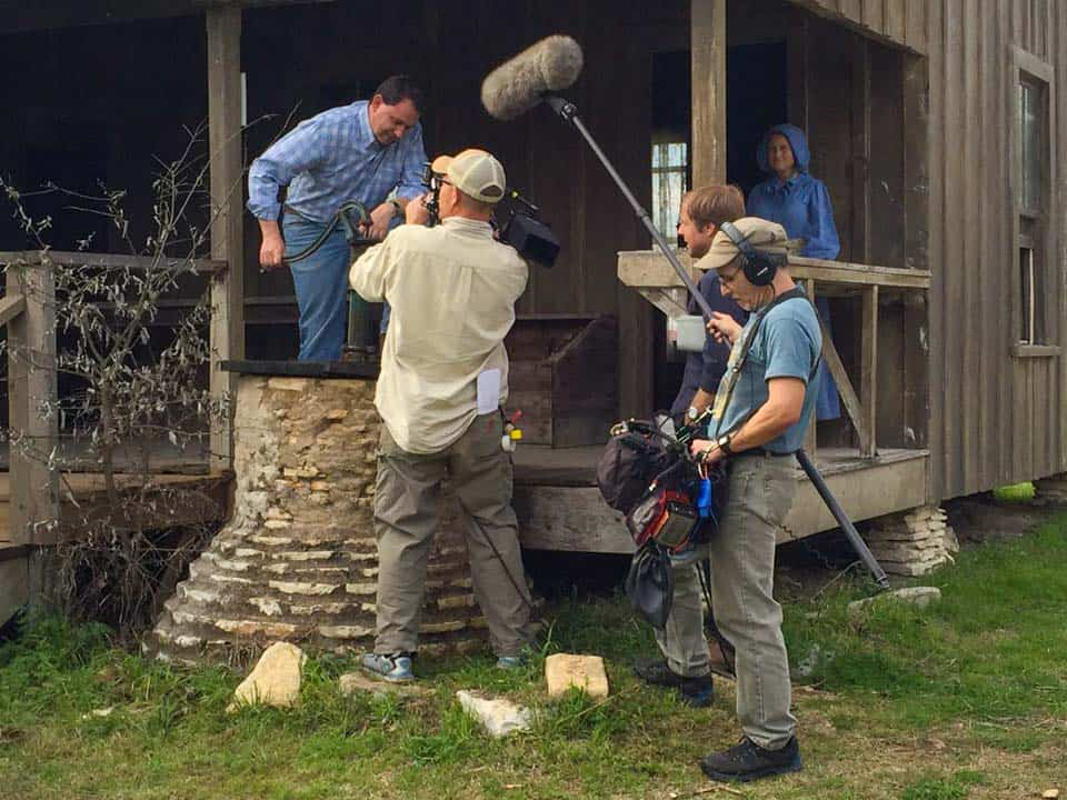A film crew films Michael Webber pumping a water well for his PBS series.