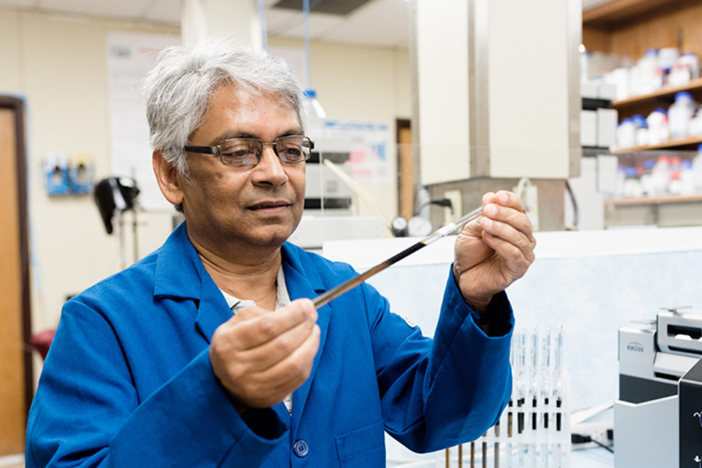 Kishore Mohanty in the lab, holding a vial of oil