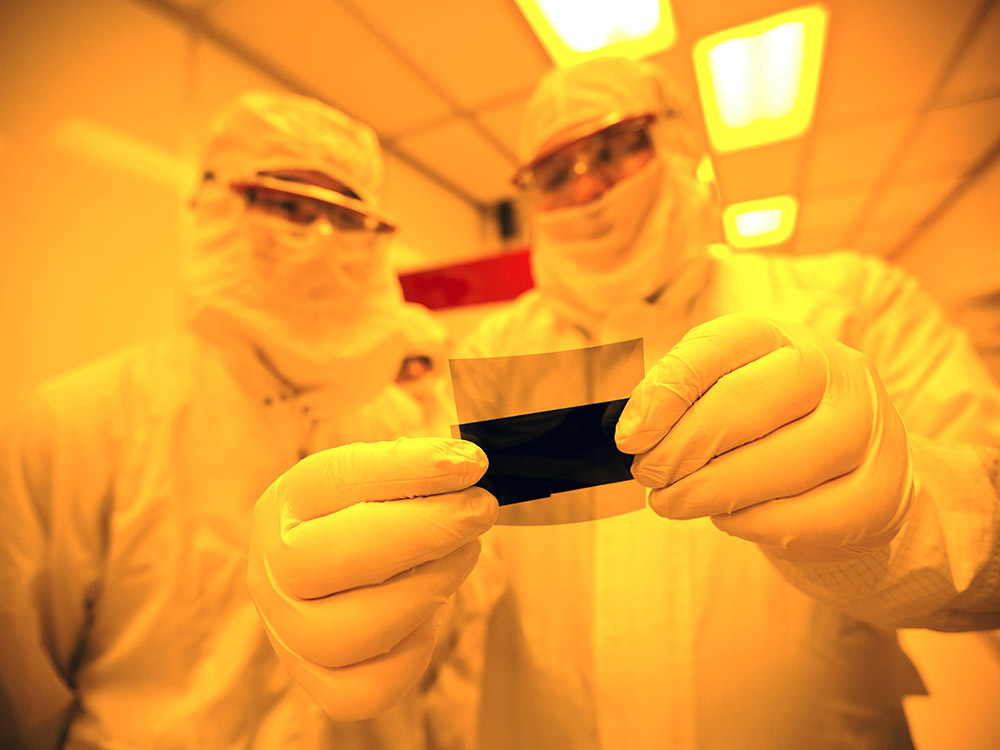 researchers in clean room with material
