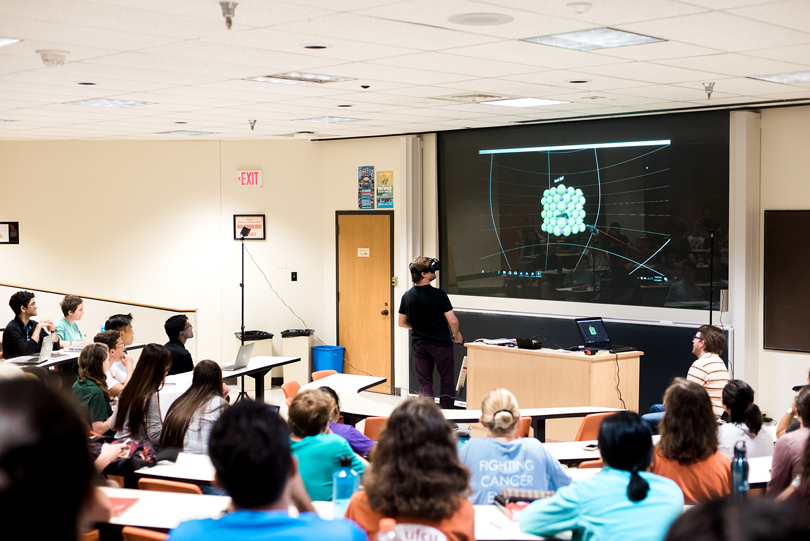Brian Korgel addresses a lecture hall full of students while wearing a virtual reality headset.