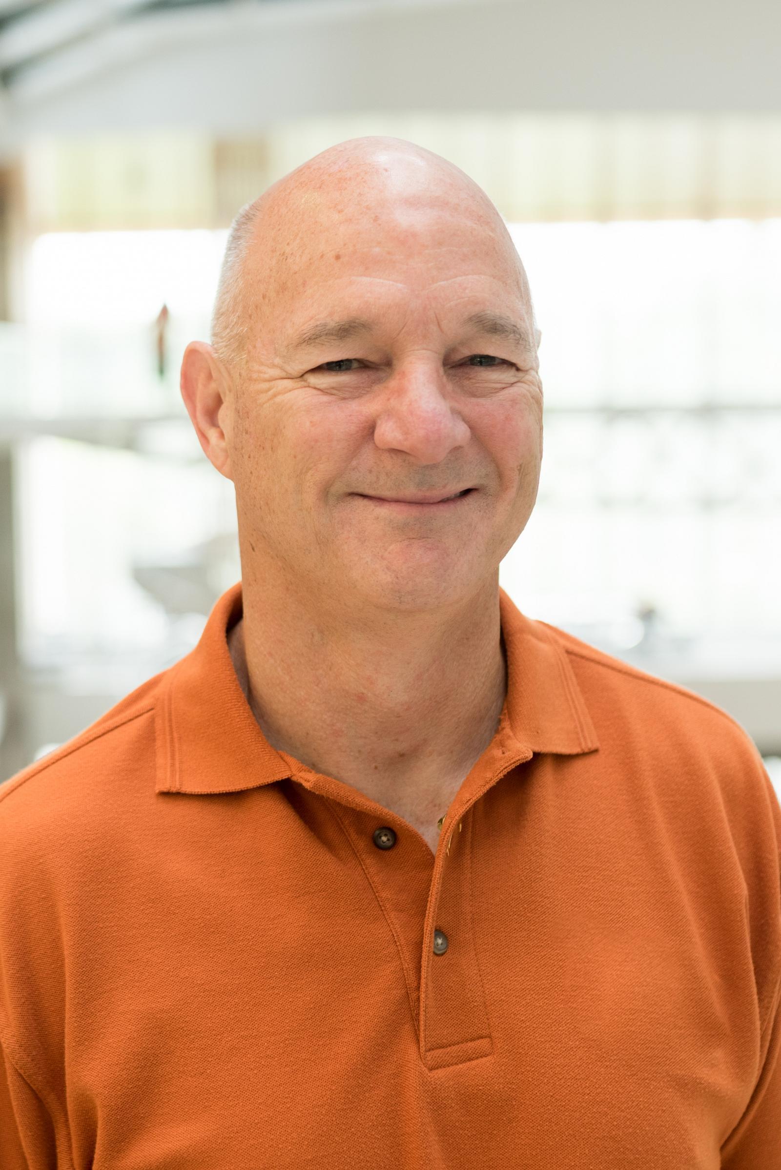 Portrait of alumnus Jimmy Canning, wearing a burnt orange polo