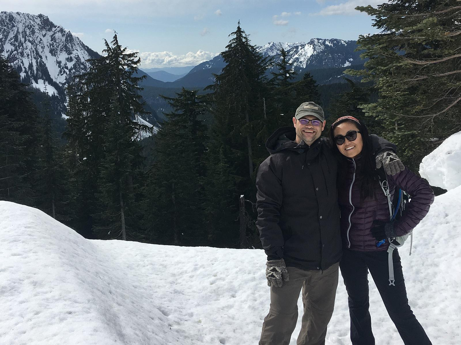 Peter with his arm around Ru in a picture of them on a snowy mountain top during a trip.