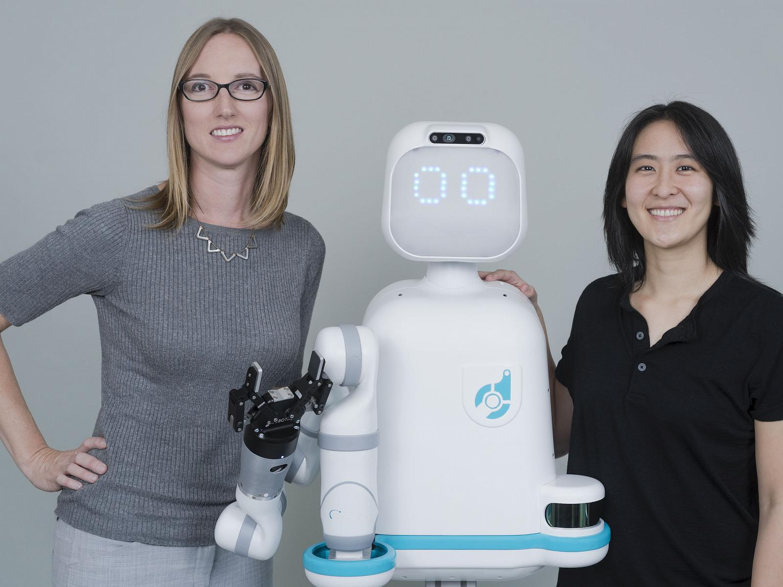 Andrea Thomaz standing next to robot