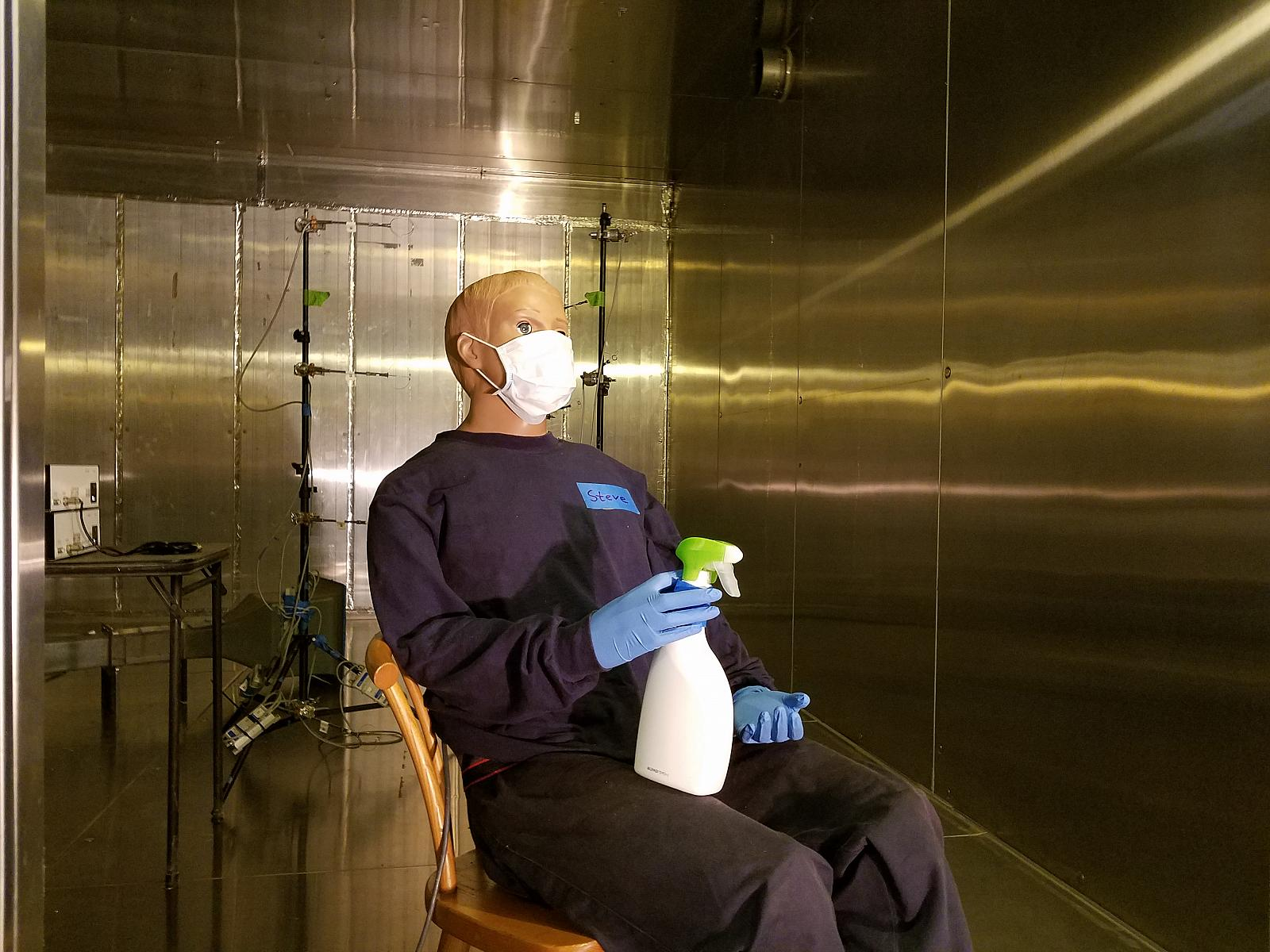 dummy in metal room sitting with spray bottle in hand
