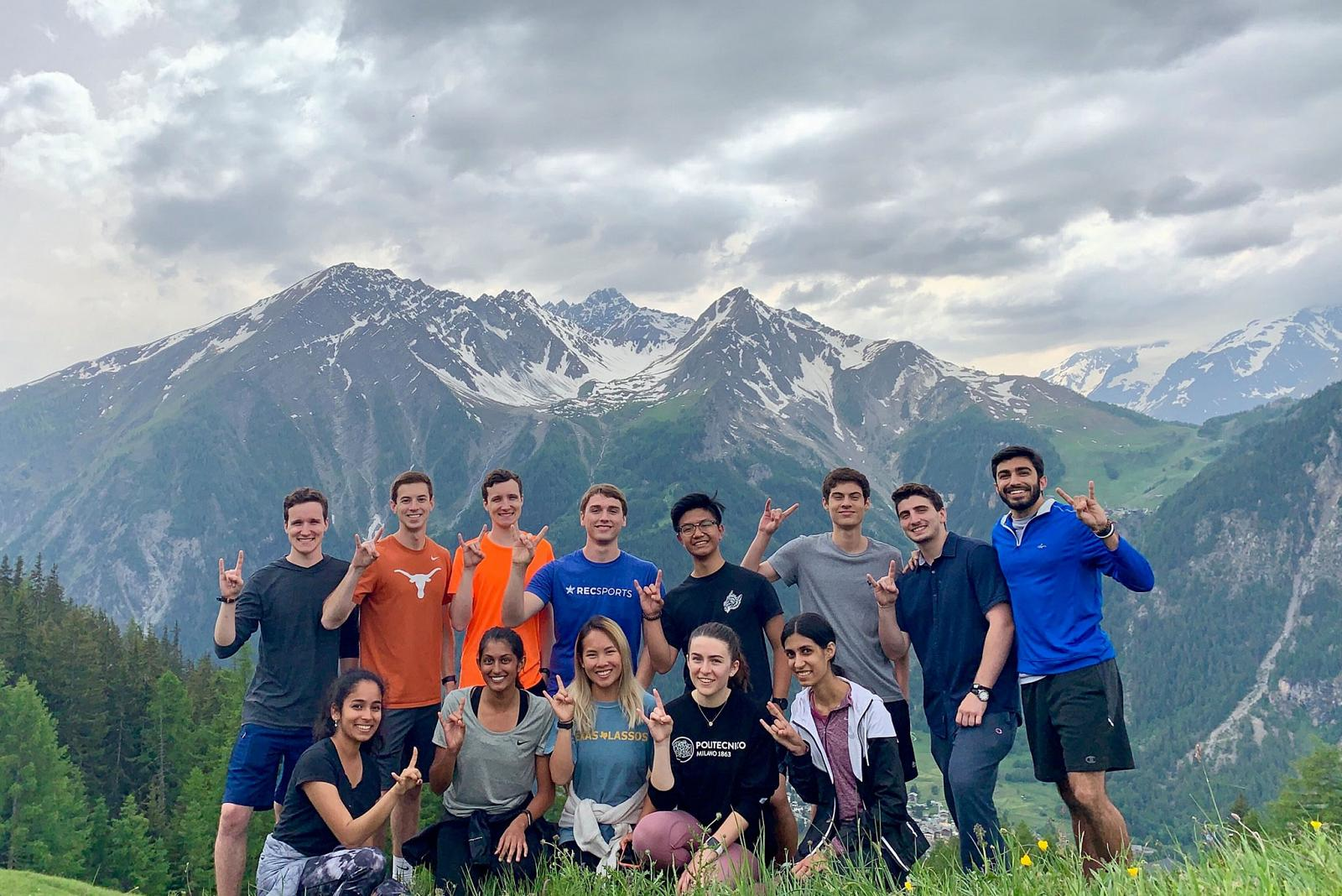 students smiling in front of a mountain